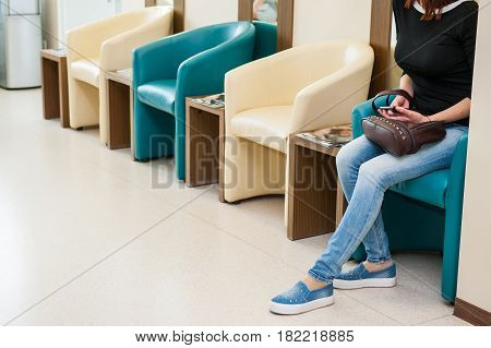 Young Girl Sitting In Waiting Room On The One Of Row Of Blue And Ivory Chairs In Hall. Selective Foc