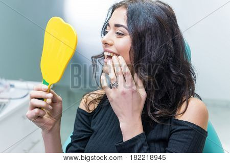 Lady checking teeth in mirror. Young female at dentist office. New dental implants.