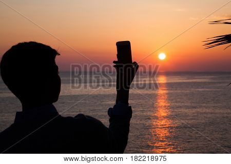 silhouette of boy taking pictures of beautiful sunset over sea with smarthone