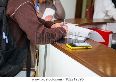 Close Up Of A Woman Hand Writing Or Signing In A Document On A Reception Zone Of Clinic. Selective F
