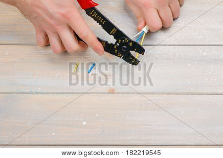 Cutting electric wires to the desired length with a special electrician tool.