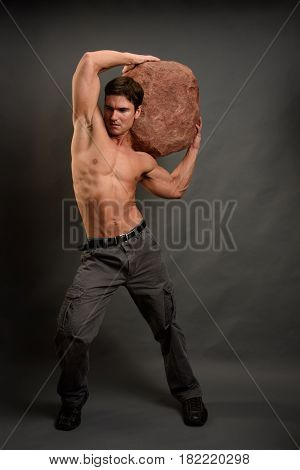 The handsome strong warrior is holding a stone.