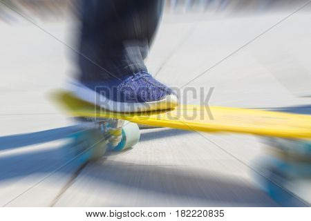 A teenager rides on a yellow pennyboard. Radial zoom blur action effect.