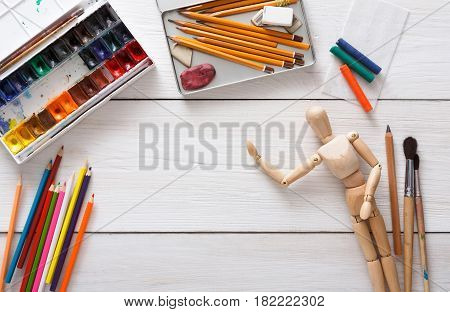Drawing tools, stationary supplies, workplace of artist. Paints and wooden painter man with brushes on white desk, top view, flat lay, objects
