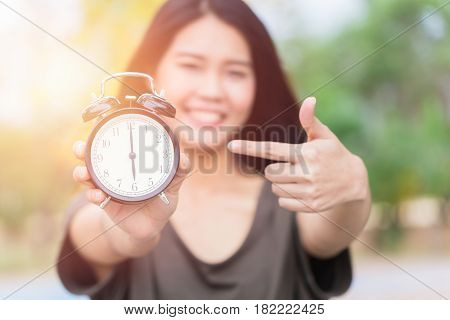 Asian women hand and point finger to retro clock times at 6 o'clock It's time to do something concept