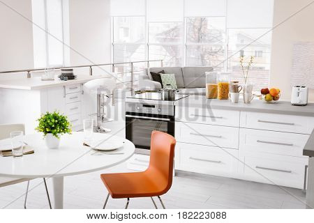 Modern kitchen interior of studio apartment with large counter and white round table