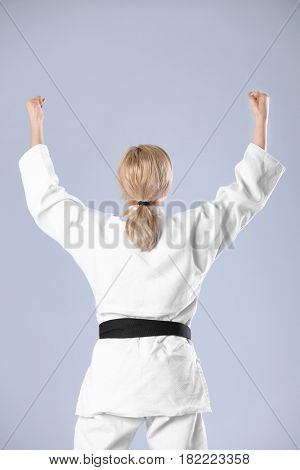 Young sporty woman in kimono on light background