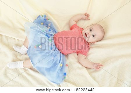 Portrait of adorable baby in tulle skirt on light background