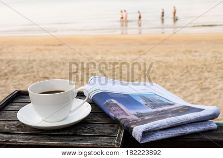 Close up white coffee cup on wood table at sunrise sand beach with newspaper in the morning Thailand