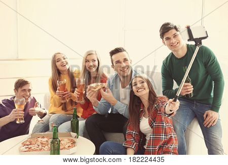 Friends taking selfie while eating pizza at home party