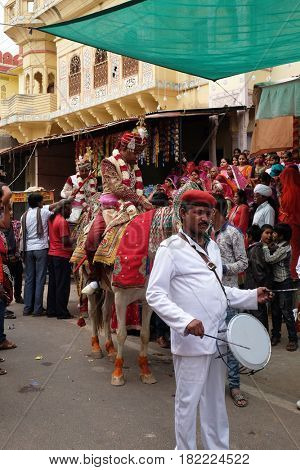 PUSHKAR, INDIA - FEBRUARY 17: Young groom on a horse leads the wedding party to the bride's house in Pushkar, Rajasthan, India on February 17, 2016.