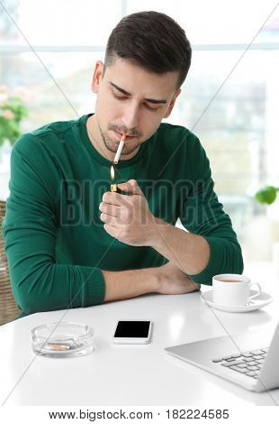 Young man sitting at table and lighting cigarette