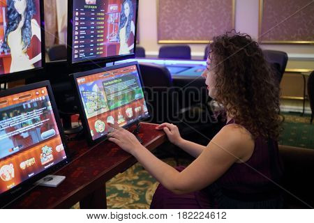 MOSCOW - OCT 17, 2016: Woman (with model release) plays electronic gaming machine in bookmaker and poker club Bingo Boom