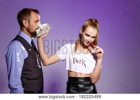 Handsome man in suit with cake on face and young beautiful brutal girl holding chilli over purple background. Copy space.