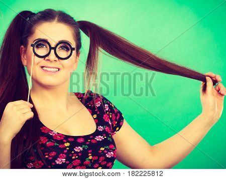 Happy young teenage woman holding fake eyeglasses on stick having fun. Photo and carnival funny accessories concept.