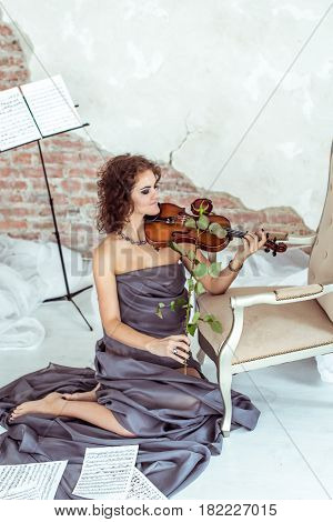 beautiful woman sitting on the floor near a chair and playing the violin bow rose instead in studio