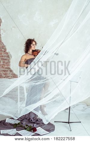 Side view beautiful woman sitting on a white chair and playing the violin in studio