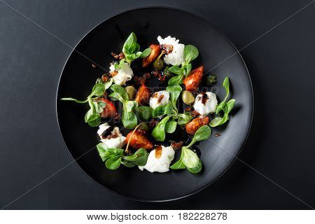Caprese salad with mozzarella tomato basil and balsamic vinegar arranged on black plate and dark background. Top view.