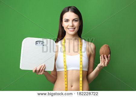 Beautiful young woman with coconut and scales on color background