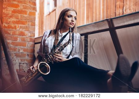 Young attractive girl sitting in white shirt with a saxophone - outdoor in old town. Sexy young woman with sax watching at camera.