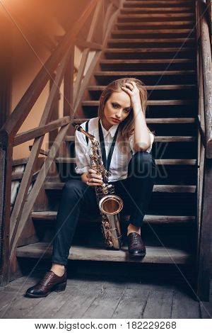 Young attractive girl sitting on stairs in white shirt with a saxophone - outdoor in old town. Sexy young woman with sax thinking about something.