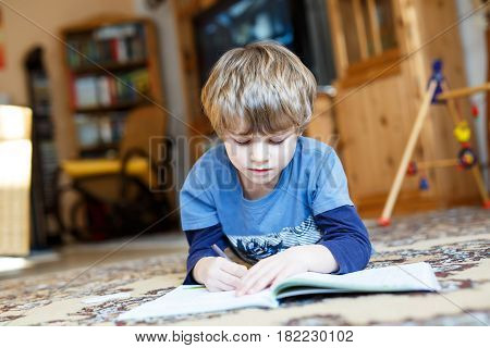 Portrait of cute happy school kid boy at home making homework on floor.. Little child writing with colorful pencils, indoors. Elementary school and education. Kid learning writing letters and numbers.