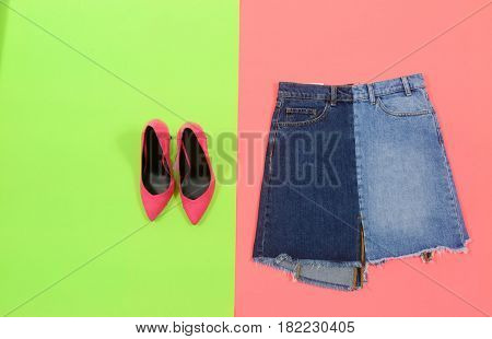 Blue denim skirt with pink shoes isolated green and pink background