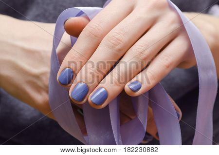 Beautiful female hand with purple nail design.