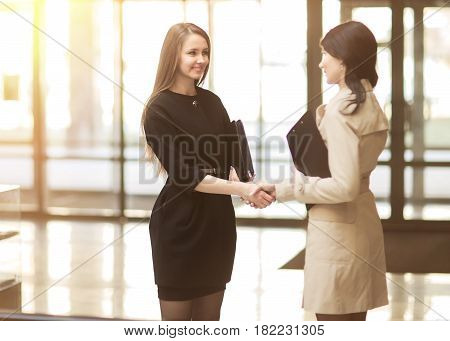 handshake of the company manager and the client in the lobby of the modern office. The photo has an empty space for your text