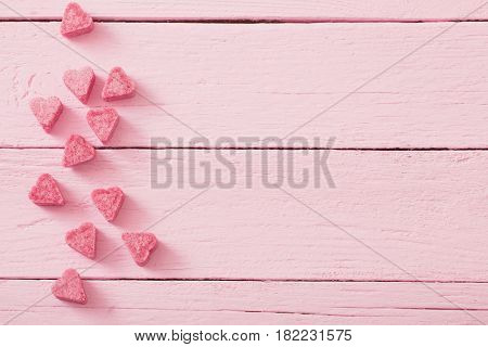 Granulated pink sugar in the shape of heart on a wooden background