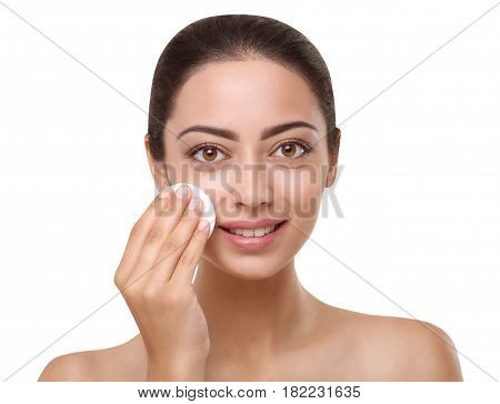 Beautiful indian girl with perfect skin removes make up with cotton pad, face cleaning concept. Beauty and health care. Ideal portrait of brunette, isolated on white background