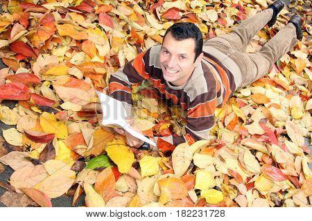 man reading on autumn floor