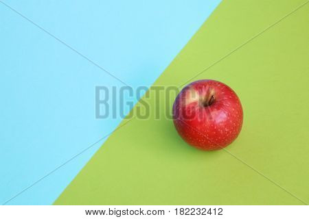 Red apple on pastel background with room for copy.