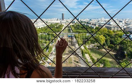 Girl is looking at Paris from the top of the Eiffel tower