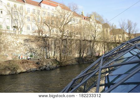 GRAZ, AUSTRIA - MARCH 20, 2017: Promenade of the river and part of the construction of crystal and steel of floating platform of the Mur Island in Graz the capital of federal state of Styria Austria.