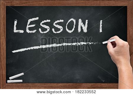 """Lesson 1"" White chalk text write on chalkboard or school blackboard with male teacher hand hold chalk writing posture"