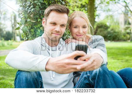 Young couple in park looking at smart phone