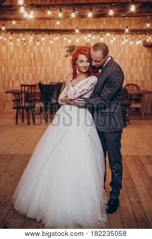 Stylish Groom And Happy Bride Gently Hugging Under Retro Bulbs Lights In Wooden Barn. Rustic Wedding