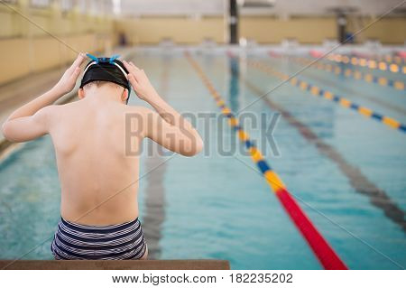 Cute little boy ready to dive in the sport swimming pool. Indoors. Sport activities for children. Training for competition.