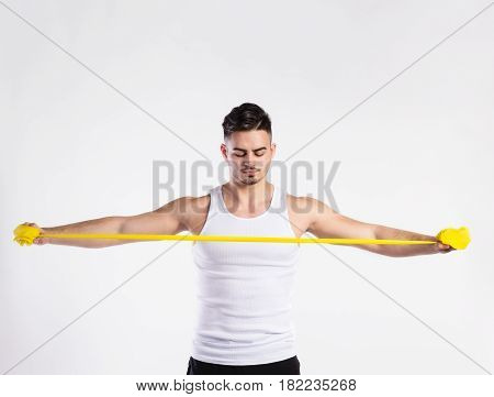 Young handsome fitness man in white sleeveless shirt working out with rubber band. Studio shot on gray background.