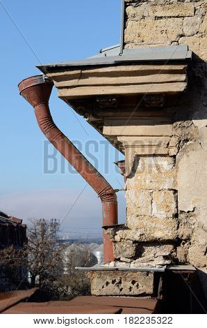Old rain pipe on abandoned building facade