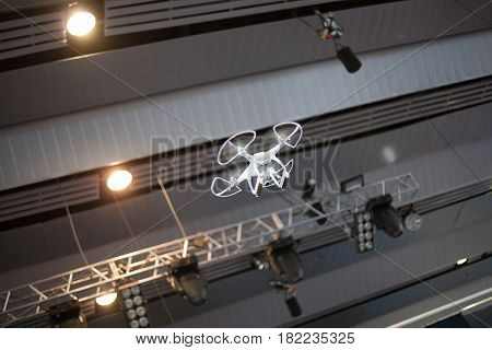 White drone in motion. Quadrocopter flying from the ceiling inside the building