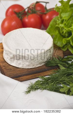 Camembert cheese on wooden board with tomatoes and green salad. Serving French homemade soft cheese. Food concept