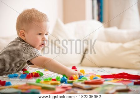 Cute preschooler child boy plays with mosaic at home. A blond little toddler playing in kid's room. Leisure activities. indoors. Boy sorting colorful children's plastic mosaic. Development.
