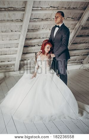 Stylish Groom And Happy Bride Gently Hugging, Tender Touch In White Wooden Room. Emotional Romantic