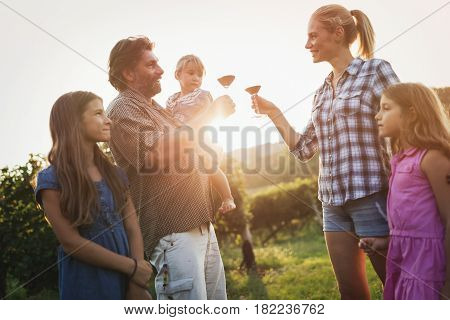 Winemaker family happy together in vineyard before harvesting