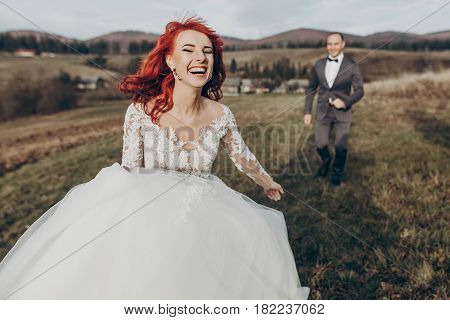 Happy Stylish Bride And Groom Running And Having Fun In Mountains At Sunset Light. Gorgeous Newlywed