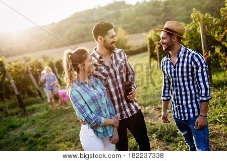 Happy young people tasting wine in vineyard
