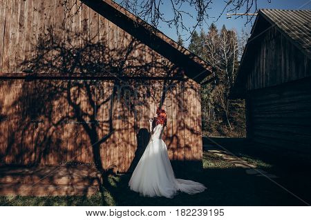 Stylish Bride Relaxing In Sunlight On Background Of Wooden Wall In Country. Rustic Wedding Concept I