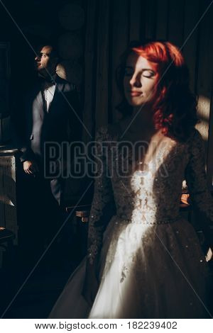 Stylish Bride And Groom Posing In Light And Shadow, Creative Photo, On Background Of Wooden Wall In